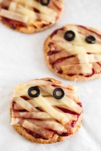 Vegan Halloween Mini Mummy Pizzas - You're going to love these vegan Halloween mini mummy pizzas. This recipe is so simple and we've used homemade spelt flour pizza dough.