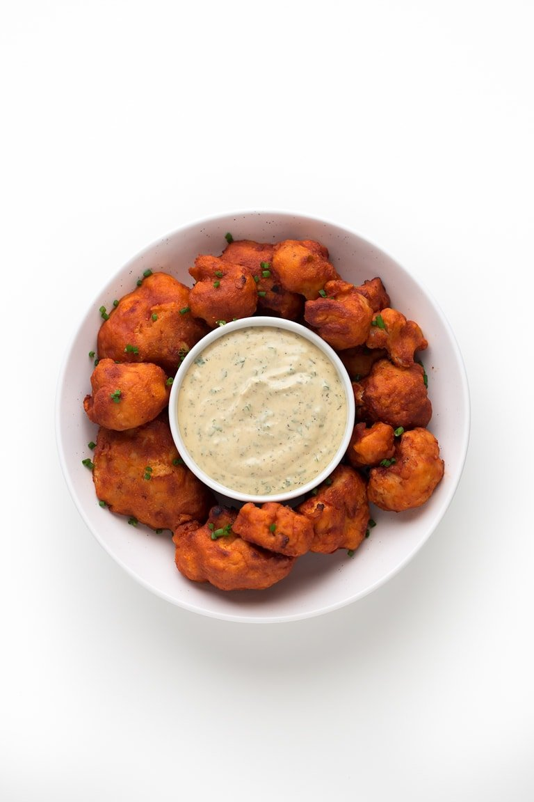 Photo of a bowl of buffalo cauliflower wings taken from the above