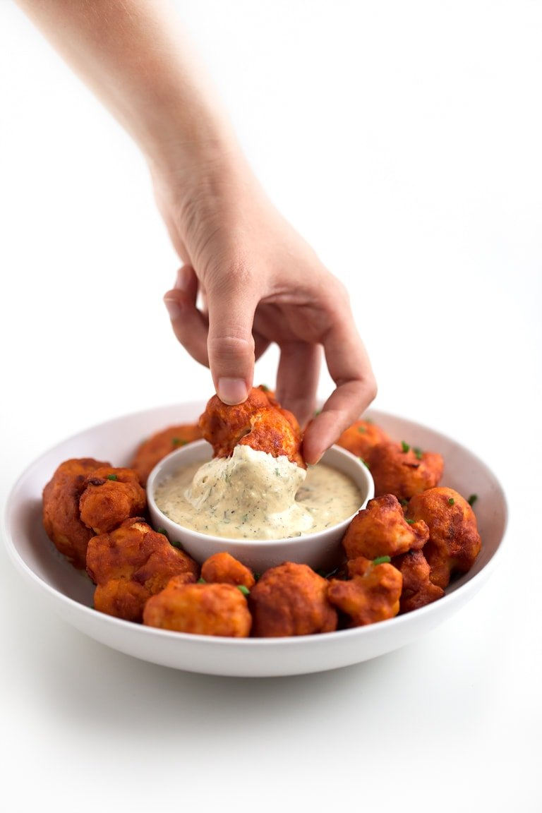 Photo of a plate of buffalo cauliflower wings being dipped in vegan ranch dressing