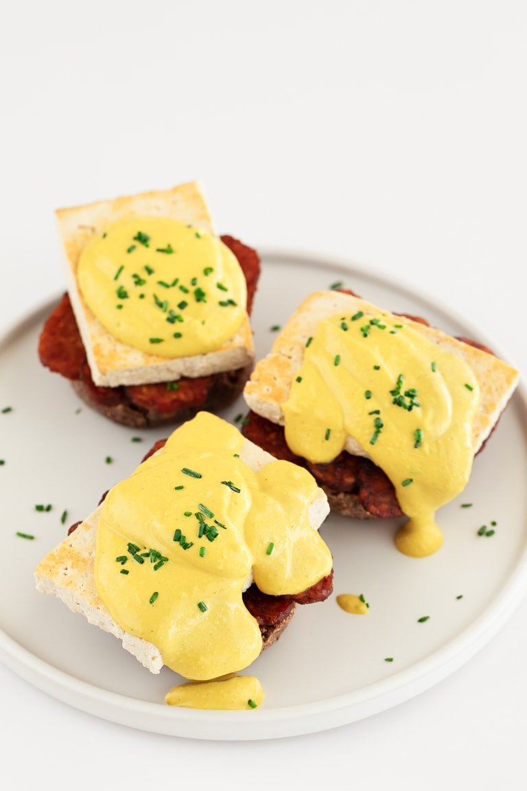 Vegan Eggs Benedict. - Vegan eggs Benedict, made with tempeh bacon, tofu and vegan hollandaise sauce. It's a delicious brunch or breakfast plant-based recipe. #vegan #simpleveganblog