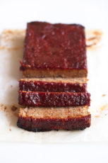 A picture of a sliced vegan meatloaf onto a white surface