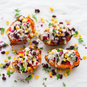Vegan Stuffed Sweet Potatoes - 7-ingredient vegan stuffed sweet potatoes with black beans, corn, tomato, onion, parsley and a creamy tahini dressing. A hearty gluten-free dinner recipe. #vegan #glutenfree #simpleveganblog