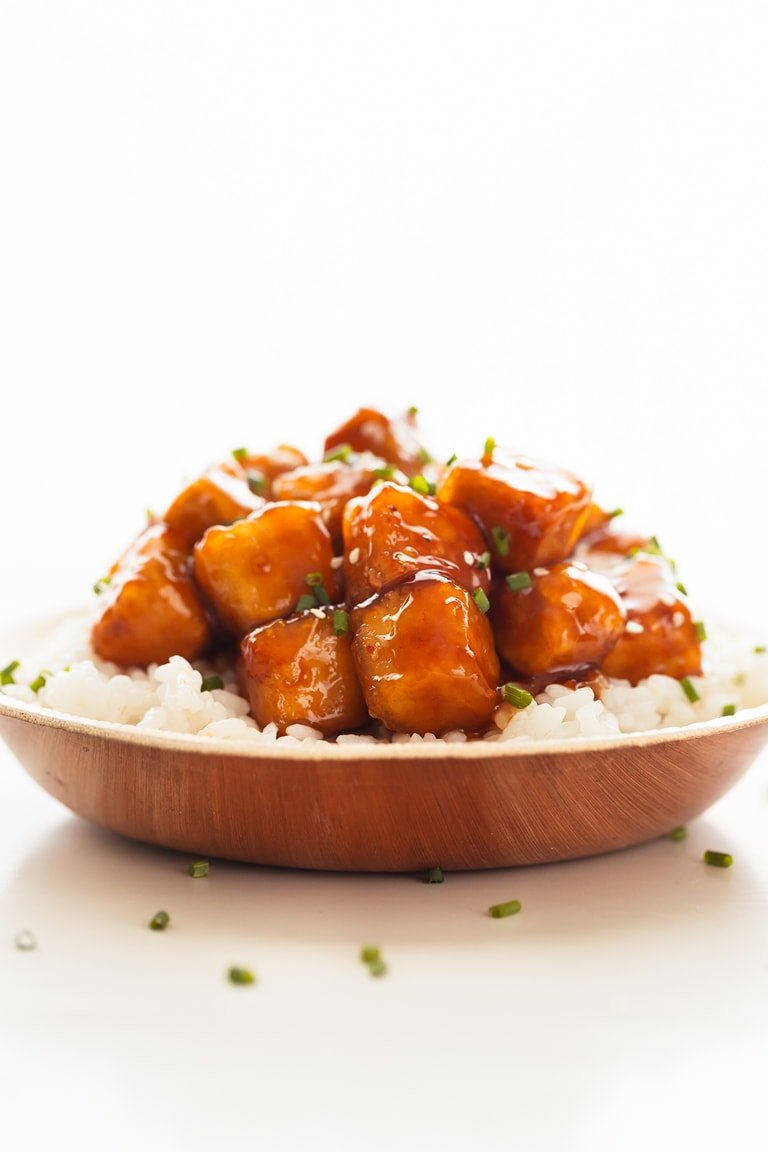 A side shot of a dish with General Tso's tofu served onto cooked white rice