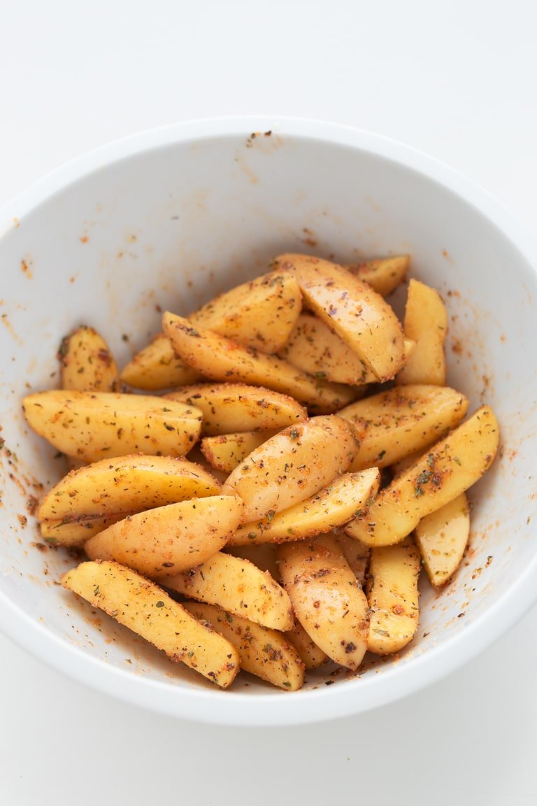 Baked Potato Wedges - Baked potato wedges, a delicious, vegan, gluten-free side dish that only requires 7 ingredients and 30 minutes. They're crisp in the outside and soft in the inside! #vegan #glutenfree #simpleveganblog