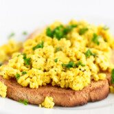 A close shot of tofu scramble topped with chopped chives on bread