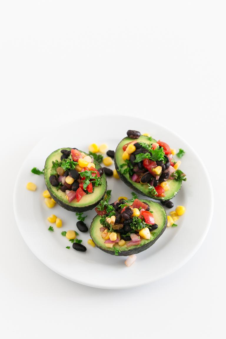 Vegan Stuffed Avocados - 7-ingredient vegan stuffed avocados, fill with black beans, corn kernels, veggies and salsa. An easy, flavorful no-cook recipe. #vegan #glutenfree #simpleveganblog