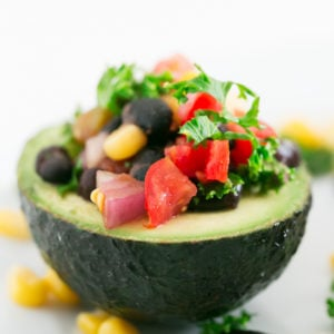 Vegan Stuffed Avocados - 7-ingredient vegan stuffed avocados, fill with black beans, corn kernels, veggies and salsa. An easy, flavorful no-cook recipe. #vegan #glutenfree #simpleveganblog