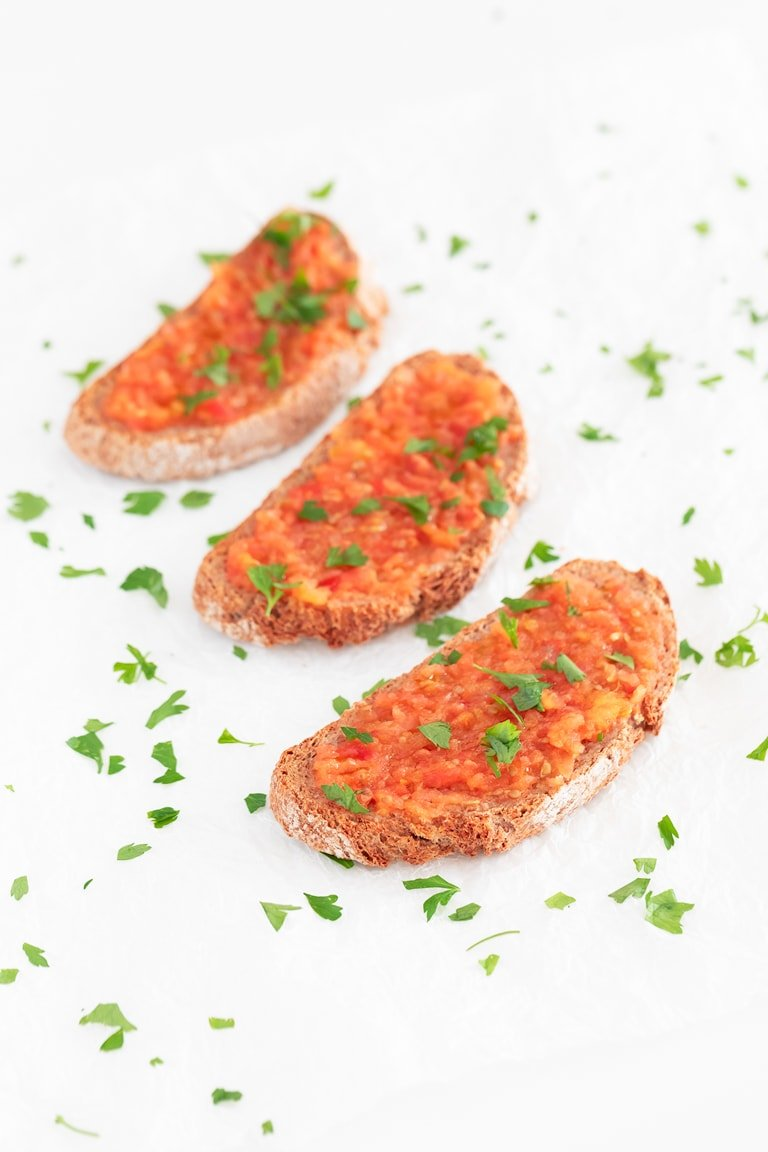 Pan con Tomate (Spanish Tomato Toast). - Pan con tomate is one of the most popular breakfast recipes in Spain. It's made with bread, garlic, tomatoes, salt and extra virgin olive oil. #vegan #simpleveganblog