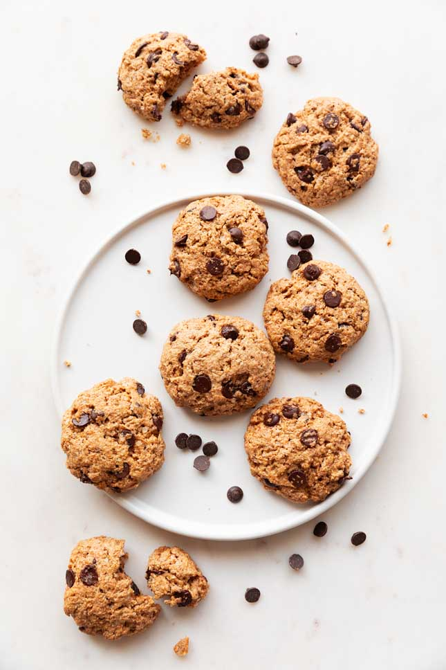 An overhead shot of a dish with vegan chocolate chip cookies on top