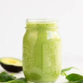 A side shot of a glass container with avocado smoothie