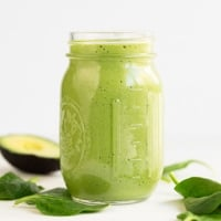 A square picture of a glass container with avocado smoothie