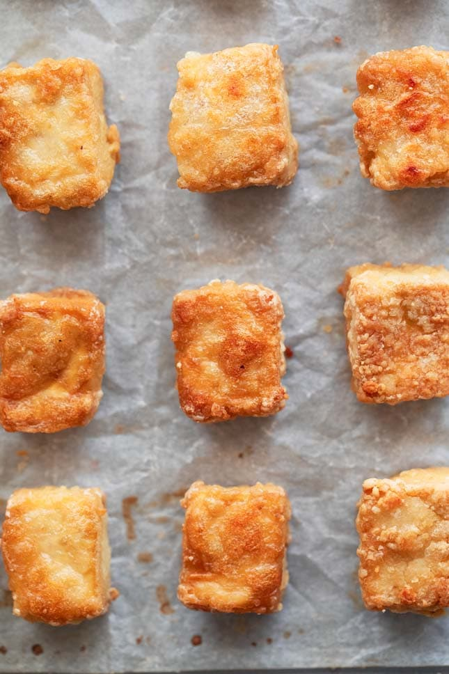 Photo of some baked tofu cubes on a lined baking sheet