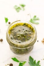Photo of a little glass that contains chimichurri sauce