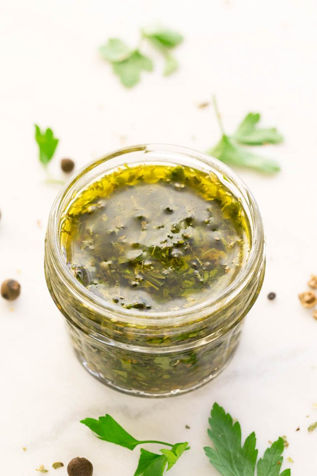 Photo of a little glass with chimichurri sauce in it