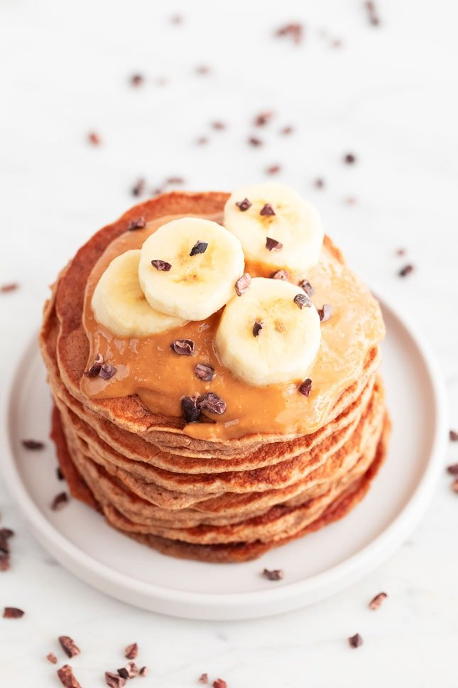 An overhead shot of a dish with vegan banana pancakes with sliced banana, peanut butter and chocolate chips on top