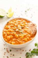 Photo of a bowl of homemade chickpea curry served with some bread