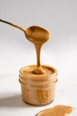 A side shot of a jar with cashew butter and a spoon