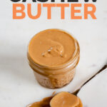 A picture of a jar and a spoon with cashew butter and the words cashew butter