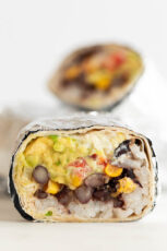 Close-up photo of a vegan burrito cut in half and wrapped in foil