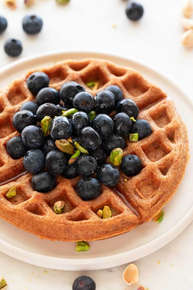 A picture of a with with homemade vegan waffles topped with blueberries and pistachios