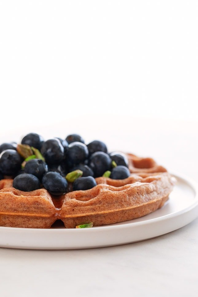 A side shot of a dish with a vegan waffles toped with maple syrup, fresh blueberries and pistachios