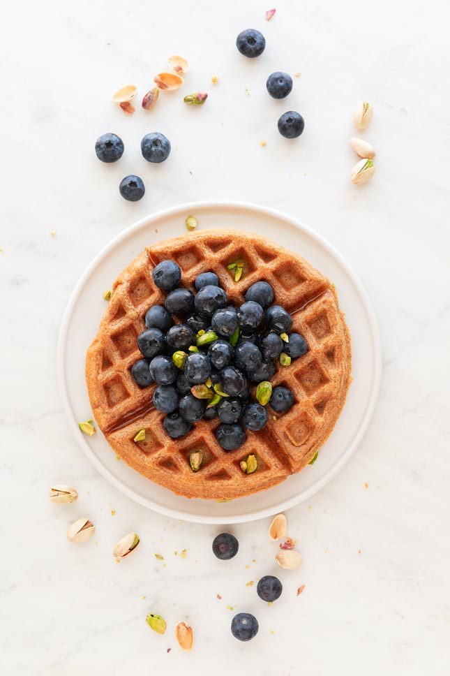 An overhead shot of a vegan waffle topped with blueberries, pistachios and maple syrup