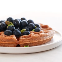 A square picture of a dish with a vegan waffles toped with maple syrup, fresh blueberries and pistachios