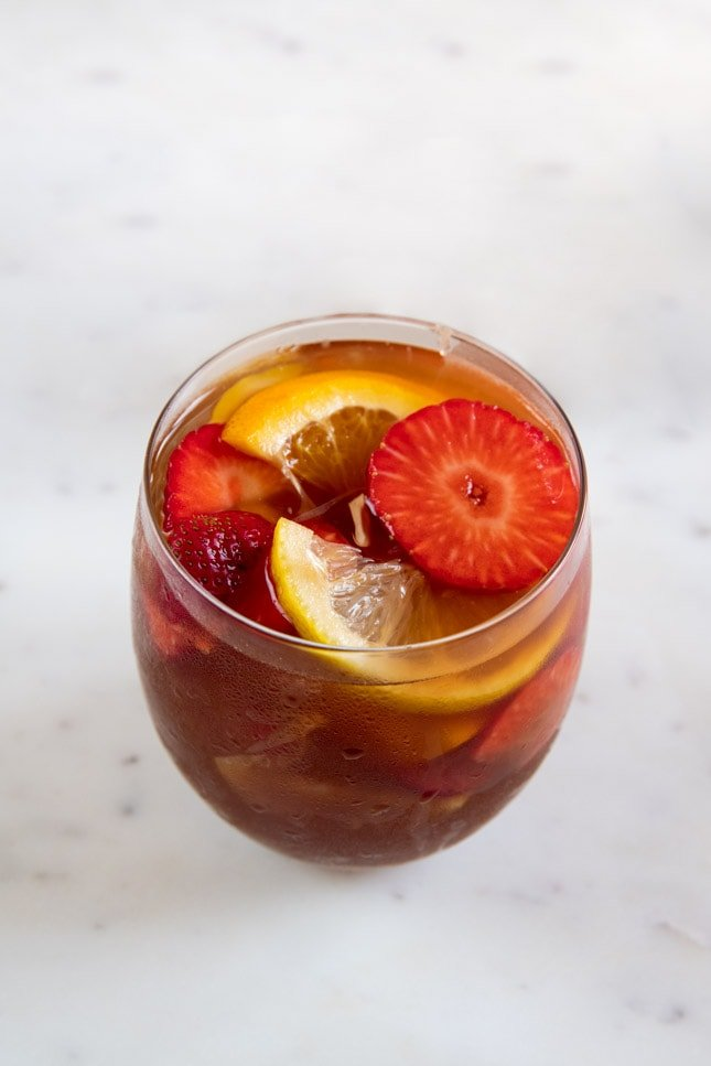 A picture of a glass with fresh fruit, ice cubes and white sangria