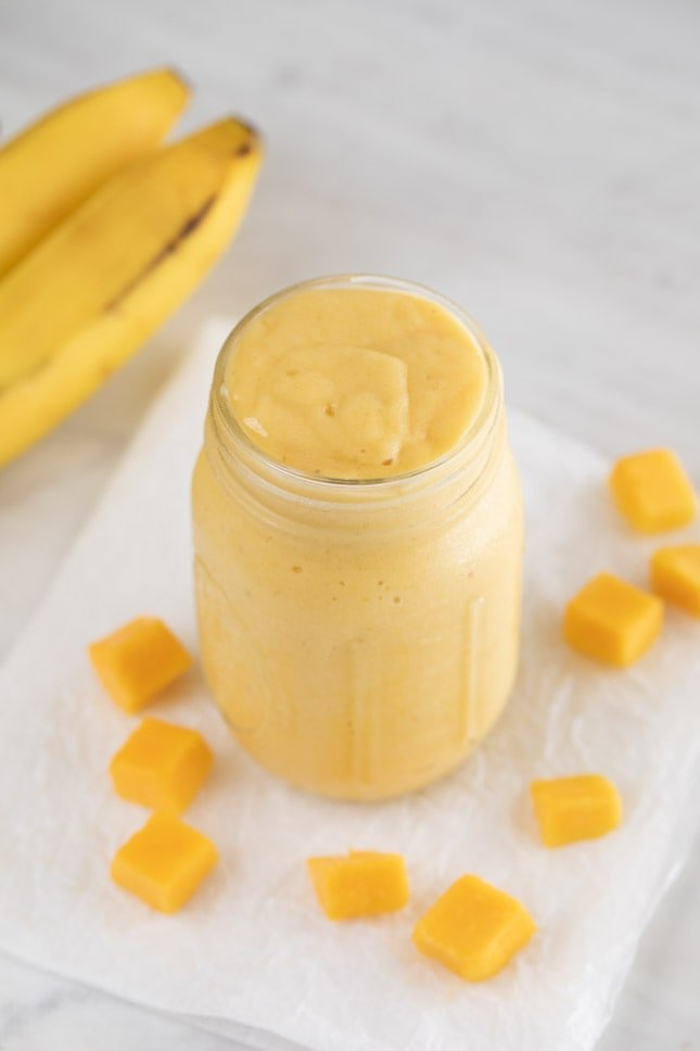 An overhead shot of a Mason jar with mango smoothie