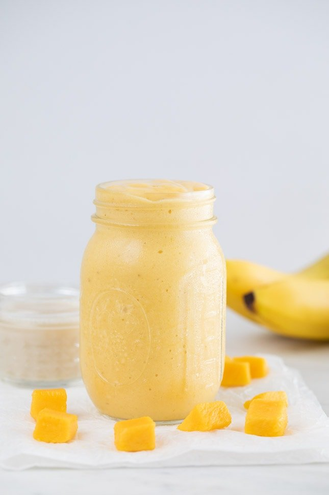A side shot of a glass jar with mango smoothie