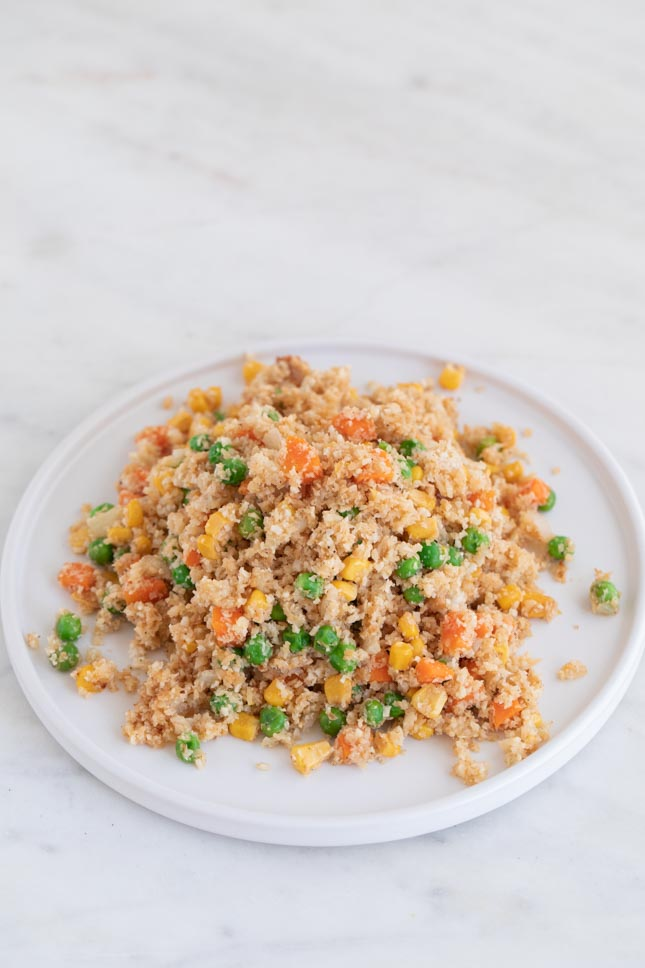 A picture of a white dish with some cauliflower fried rice