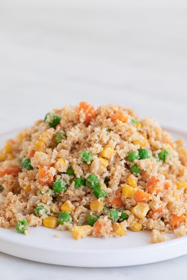 A close shot of a white dish with some cauliflower fried rice
