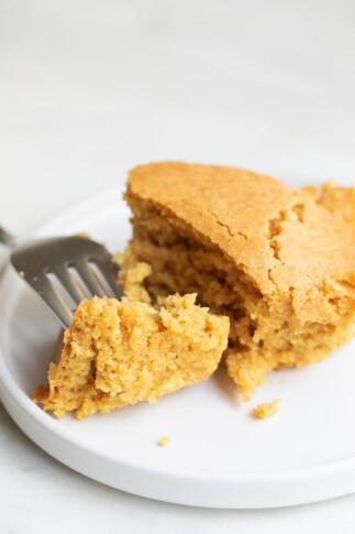 A close shot of a dish with some vegan cornbread and a fork