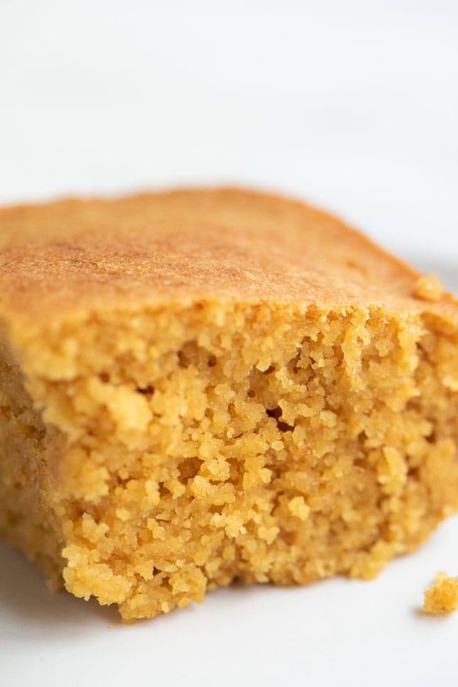 A side shot of a small dish with a piece of vegan cornbread