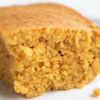 A square picture of a small dish with a piece of vegan cornbread
