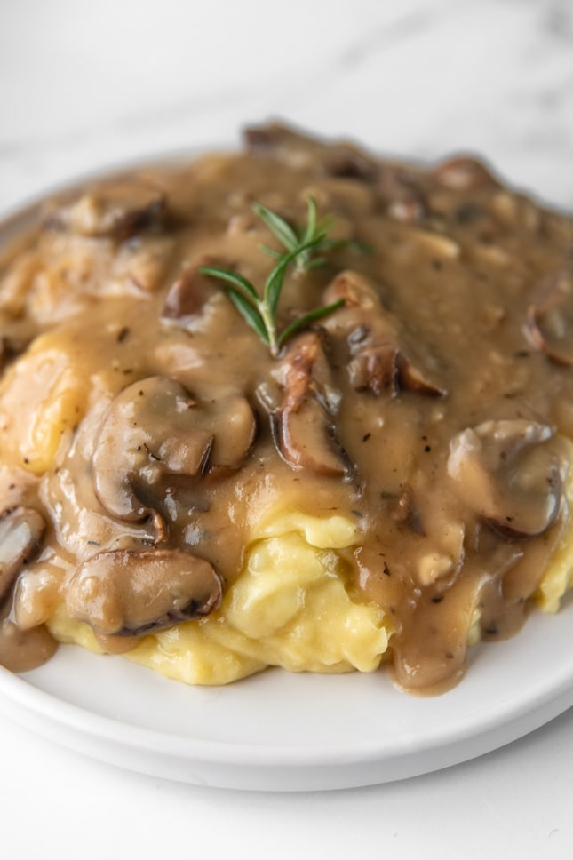 Close-up shot of mushroom gravy served over some mashed potatoes