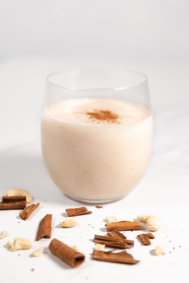 Side shot of a glass of vegan eggnog