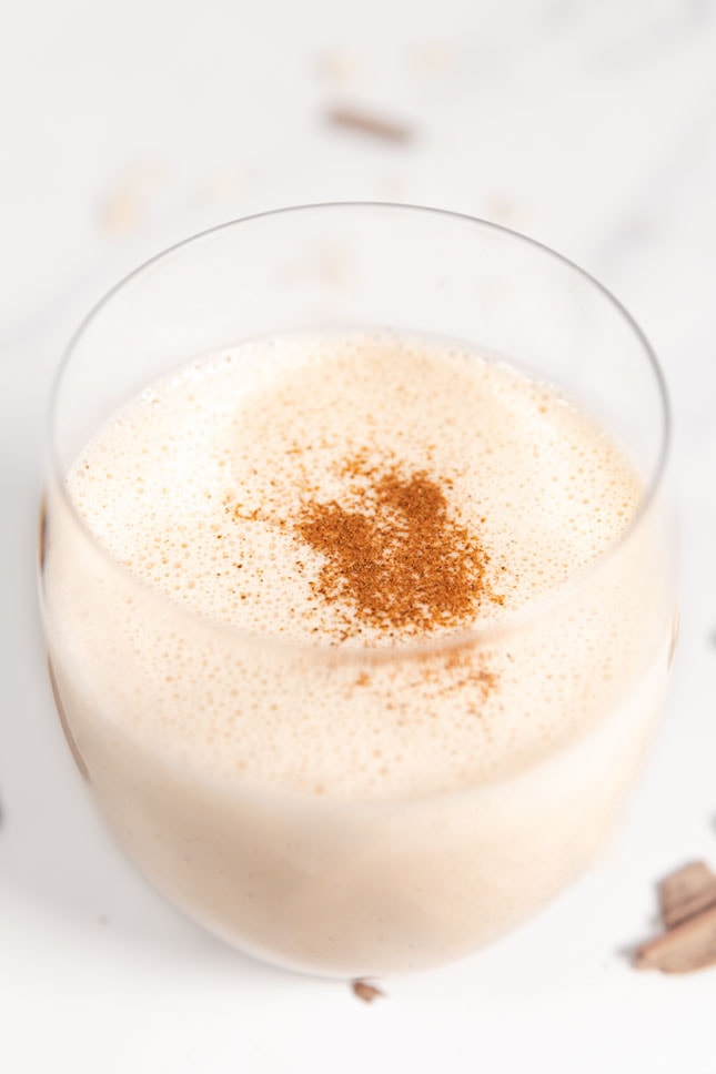 Close-up shot of a glass of vegan eggnog
