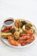 A picture of a dish with vegetable tempura and a small bowl with soy sauce