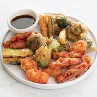 A small photo of vegetable tempura in a plate with a small bowl with soy sauce