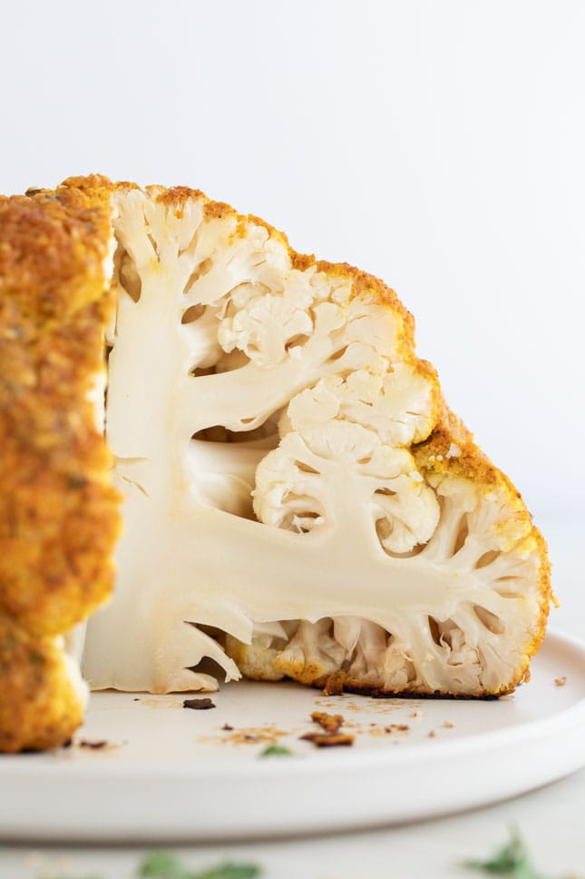 A side picture of a whole roasted cauliflower cut onto a plate