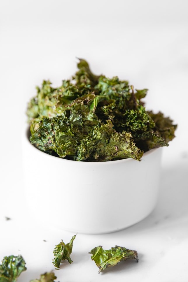Side shot of a bowl of kale chips
