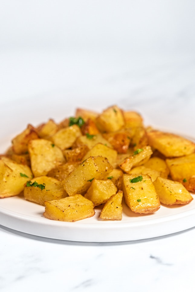 Side shot of a plate of roasted potatoes