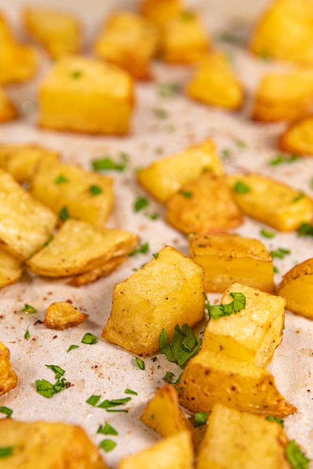 Close-up shot of a lined baking dish with roasted potatoes
