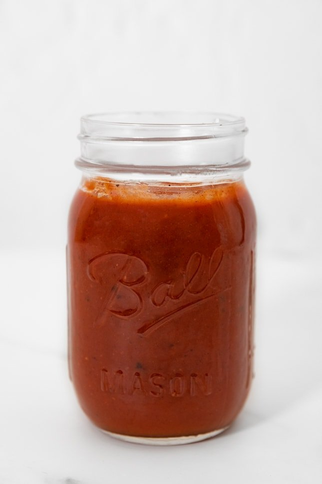 Side shot of a jar of red enchilada sauce