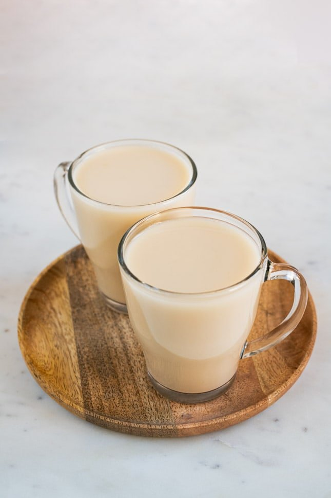 A picture of 2 mugs with homemade oat milk onto a wooden tray