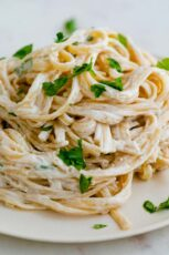 A close shot of a dish with vegan Alfredo sauce mixed with pasta and topped with chopped parsley