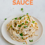 A picture of a dish with cooked spaghetti mixed with vegan Alfredo sauce and the words vegan Alfredo sauce