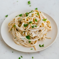 A picture of a dish with cooked spaghetti mixed with vegan Alfredo sauce