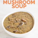 A picture of a bowl of vegan cream of mushroom soup onto a marble surface with the words vegan cream of mushroom soup